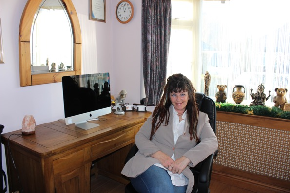 Vicky Tunaley, Hinckley hypnotherapist, smiling and sitting at her desk in her comfortable therapy room.