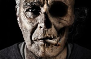 Face of a man, dark looking, smoking a cigarette. The right side of his face is skeletal.