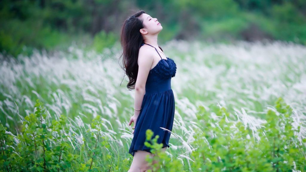 Young lady in a field with long grass., wearing a blue dress and looking up to the sky in a peaceful repose.