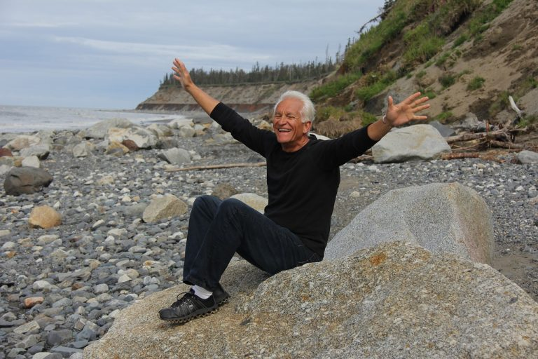 Happy older man sitting on a rock on the beach, arms spread out, smiling.