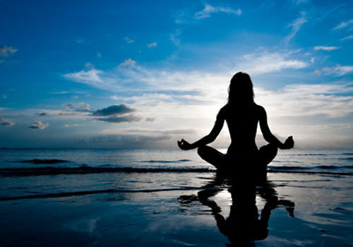 silhouette of lady meditating in lotus position on a beach