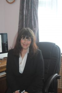 Vicky Tunaley sitting at desk, smiling