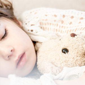 Girl asleep with teddy bear