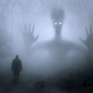 Dark misty wood with shadowy outlines of a man's silhouette walking and a larger, strange looking figure in the background, with piercing white eyes.